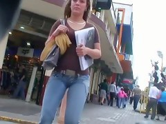 Hot body girl in penurious jeans walking the street with a voyeur behind their way